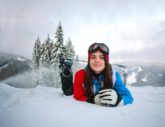 山の上に雪に覆われた森の冬の若い物思いにふける女性 Premium写真