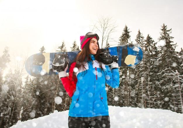 松林の降雪で冬の笑顔のスノーボーダーの女の子 Premium写真