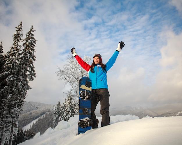 雪の冬の幸せな女の子スノーボーダーは山の上に立っています Premium写真