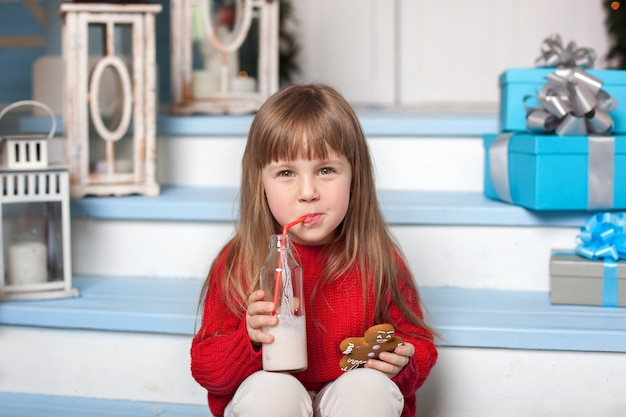 牛乳と家の近くのポーチに座っているジンジャーブレッド人の少女。子供は自宅のポーチでミルクとクッキーを食べる。牛乳とクリスマスキャンディのグラスを持つ幼児。クリスマスプレゼントの子。 Premium写真