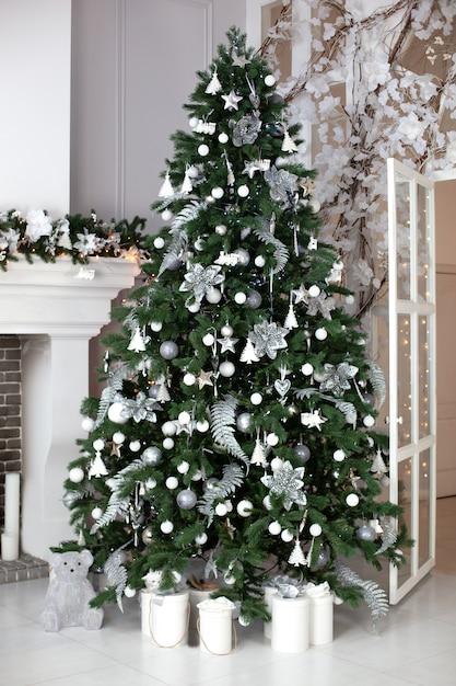 クリスマスツリーとギフトで飾られたお祝いクリスマスインテリア。ボール、ガーランド、パインガーランドが暖炉からぶら下がって飾られたクリスマスツリーとスタイリッシュなリビングルームのインテリア。新年 Premium写真