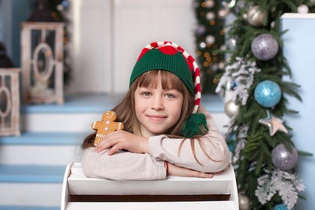メリークリスマス、ハッピーホリデー! 。手でクッキーとクリスマスのエルフの衣装での幸せな女の子。子供はサンタクロースのジンジャーブレッドマンを保持しています。帽子の陽気なエルフの肖像画。 Premium写真