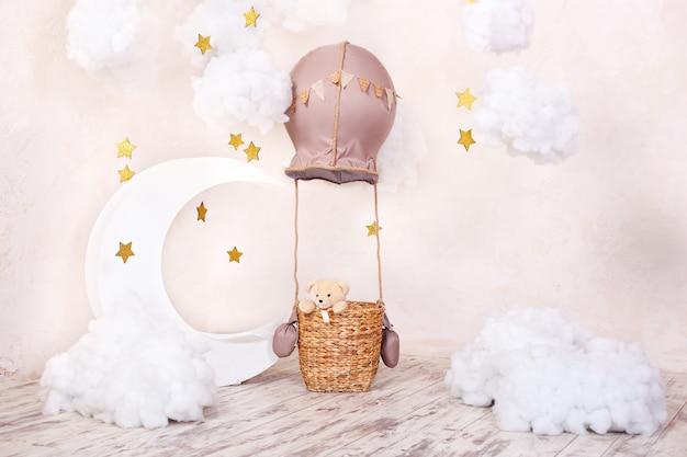 テディベアの旅行者およびパイロット。子供の頃の夢。エアロスタット、風船、織物の雲を備えたスタイリッシュなビンテージ子供部屋。子供たちの写真撮影の場所:エアロスタット、気球、雲。 Premium写真