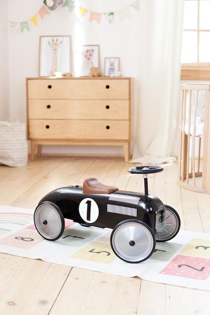 子供部屋でレトロなスタイルの子供のレーシングカー。男の子のためのレースカーの黒のビンテージモデル。魅力的な遊び場に最適な車。赤ちゃん用の輸送機器。幼稚園の子供のおもちゃの車。 Premium写真