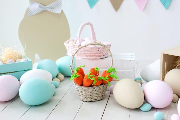 Пасхальный! много разноцветных пасхальных яиц! пасхальное украшение комнаты с кроликами и корзинками с яйцами. ферма. сбор урожая. корзина с морковью и пасхальными кроликами. пасхальный декор. праздничные флаги на стене Premium Фотографии