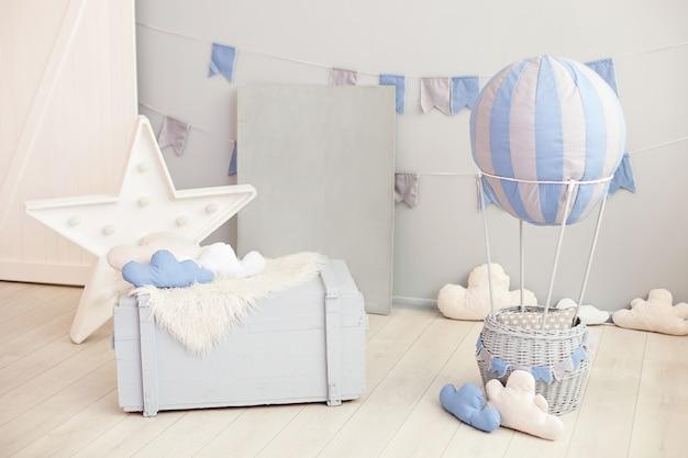 Современный винтажный интерьер комнаты для детей с деревянным комодом и воздушным шаром с облаками на белой стене с праздничными флагами. детская спальня. интерьер детского сада. простоватый Premium Фотографии