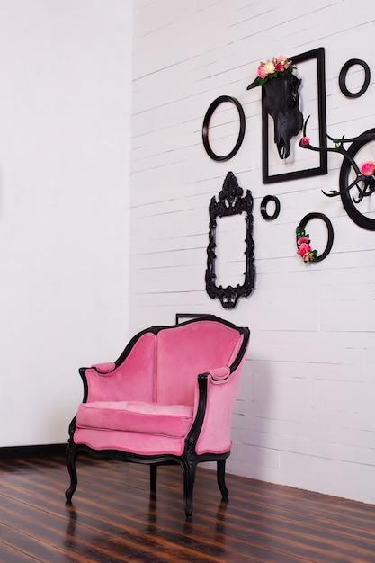 明るい部屋でビンテージベロアアームチェア。頭蓋骨と木製の壁に掛かっている角を持つさまざまな空の写真フレーム。壁の装飾の概念。インテリア、ヴィンテージ、モダン、ロフト。ゴシック様式 Premium写真