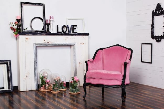 明るい部屋と人工暖炉のあるヴィンテージベロアアームチェア。木製の白い壁とインテリアの屋根裏部屋。ゴシック様式の部屋。 Premium写真