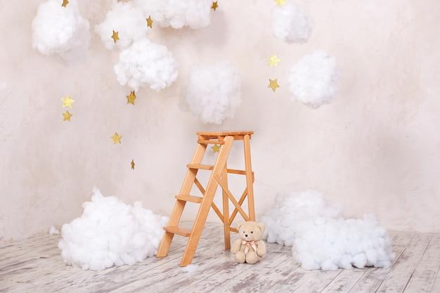 子供部屋の雲と木製の階段スツール。北欧スタイル。素朴な部屋のインテリア。クリスマスの休日の装飾。 Premium写真