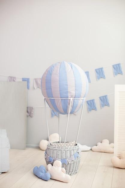 Яркая детская комната с воздушным шаром, воздушными шарами и текстильными облаками на белой стене с праздничными флагами. детская спальня. интерьер детского сада. скандинавский интерьер комнаты. деревенский декор Premium Фотографии