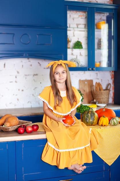 Счастливая маленькая девочка в желтом платье в осеннем декоре с тыквами на кухне, Premium Фотографии