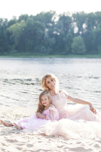 母金髪と背景に湖のある砂の上の美しいドレスで彼女の娘の肖像画。ビーチで晴れた日を楽しんで幸せな家族。家族のライフスタイル、家族愛の概念。 Premium写真