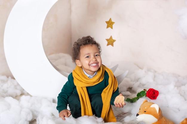 アフリカ系アメリカ人の少年の顔のクローズアップの肖像画。小さな男の子が座って笑顔します。かわいい赤ちゃん、ゲームの赤ちゃん。可愛い笑顔。巻き毛。子供時代。子供は幼稚園で遊ぶ。幼児教育 Premium写真