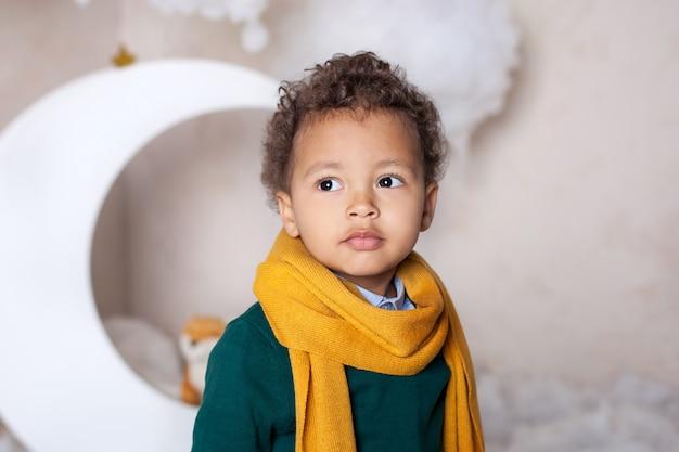 黒人少年をクローズアップ。黄色のスカーフで陽気な笑みを浮かべて黒少年の肖像画。少しのアフリカ系アメリカ人の肖像画。黒人の男。物思いにふける子。子供時代。子供は幼稚園で遊ぶ。小さな男の子の顔 Premium写真