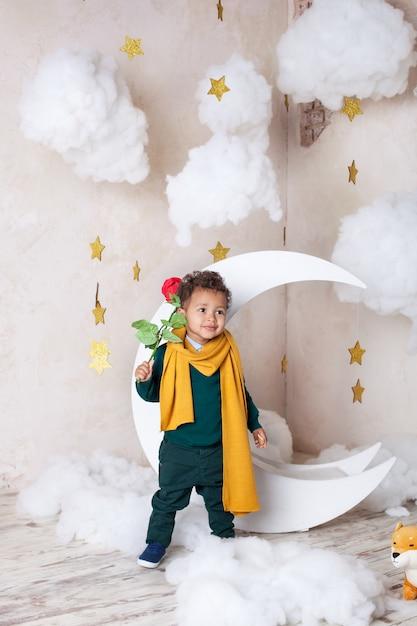 バラと小さな黒い男の子。祝日おめでとうございます。子供の想像力。少し巻き毛のアフロアメリカン。休日の概念。 Premium写真