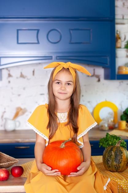 Маленькая девочка держит большую тыкву в кухне дома. сбор урожая. здоровое питание, вегетарианство, витамины, овощи. Premium Фотографии