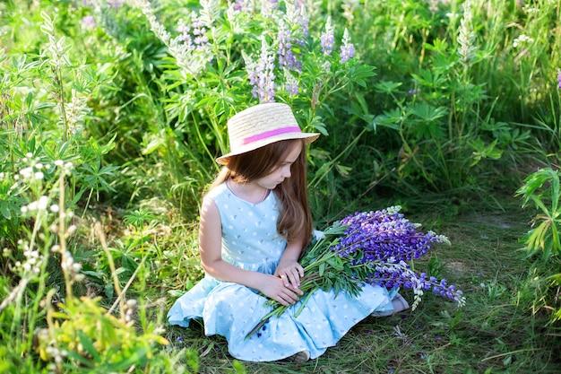 Красивая маленькая девочка в платье и шляпе в области люпинов. девушка держит большой букет фиолетовых люпинов в цветущем поле. цветущие цветы люпина. концепция природы. прованс. детство. летний отпуск Premium Фотографии