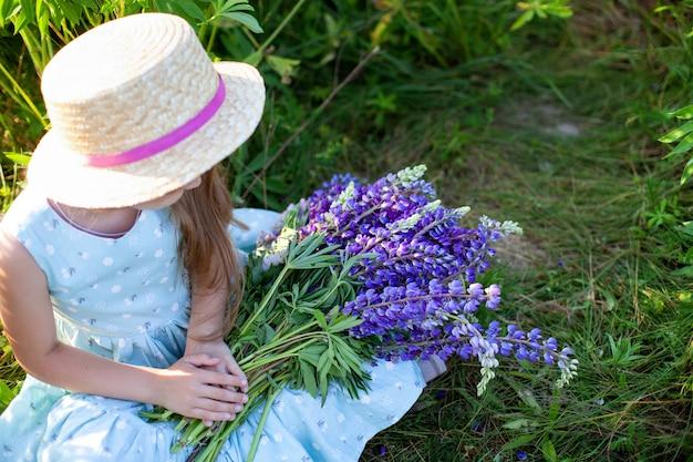 Крупным планом руки женщин, держа букет с полевыми цветами. летние фиолетовые цветы. люпиновое поле. прованс. маленькая девочка держит большой букет фиолетовых люпинов в цветущем поле. концепция природы. настоящее время Premium Фотографии