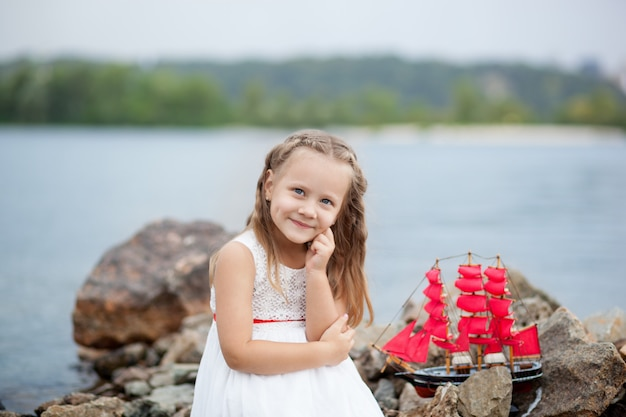 クローズアップの肖像画白いドレスと赤い帆のかわいい女の子。子供がおもちゃの船で海の上に座ります。子供の頃のコンセプトです。ビーチの砂のゲーム。残りの概念。子供が屋外でおもちゃで遊ぶ Premium写真