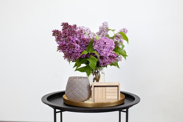 Пустой деревянный календарь рядом с букетом цветов сирени в вазе и подсвечник на старинный журнальный столик. Premium Фотографии