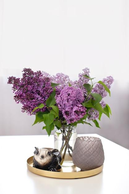 花瓶とテーブルの上の燭台にライラックの花の花束の横にあるウサギのウサギのセラミックの置物。 Premium写真