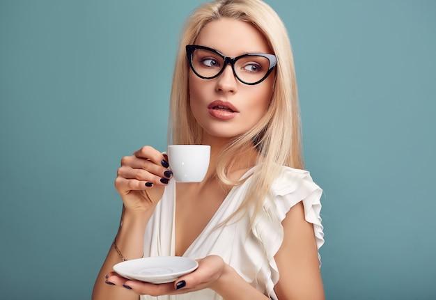 Великолепная чувственная блондинка в белом платье с чашкой кофе Premium Фотографии