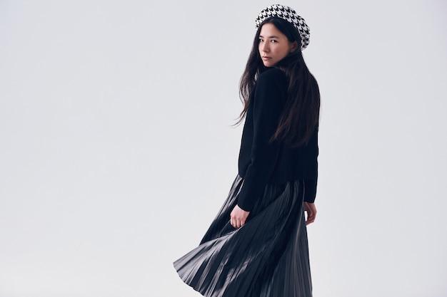 Элегантная азиатская женщина в модной черной юбке и берете Premium Фотографии