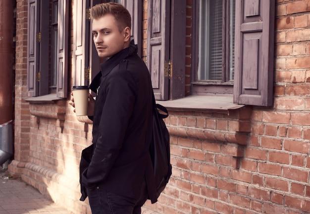 一杯のコーヒーと暗いコートで若いハンサムな男 Premium写真