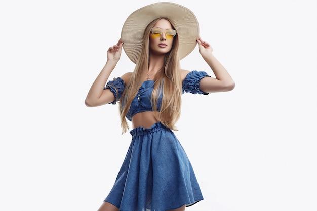 青いドレスと広い帽子でポーズ美しい女性モデル Premium写真