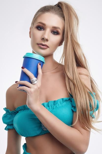 コーヒーカップと明るいスポーツ制服でゴージャスなモデルの女の子 Premium写真