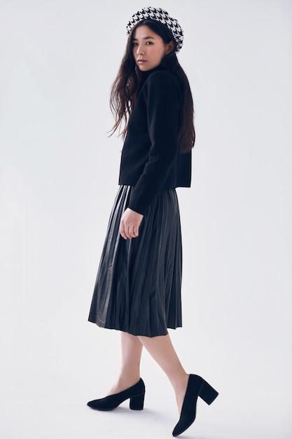 ファッショナブルな黒のスカートとベレー帽でエレガントなアジアの女性 Premium写真