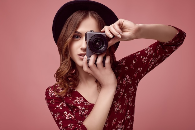 赤いドレス、黒い帽子、カメラとメガネでエレガントな内気な少女 Premium写真