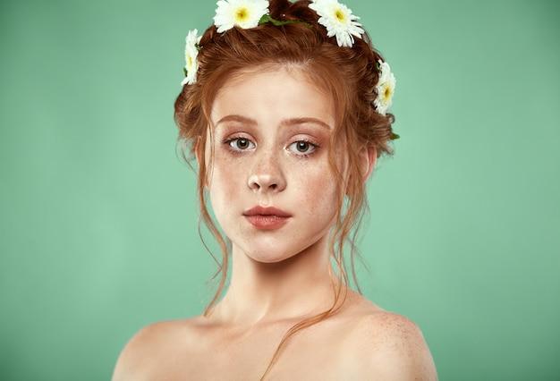 彼女の頭にカモミールクラウンと美しい肯定的な赤毛の女の子 Premium写真