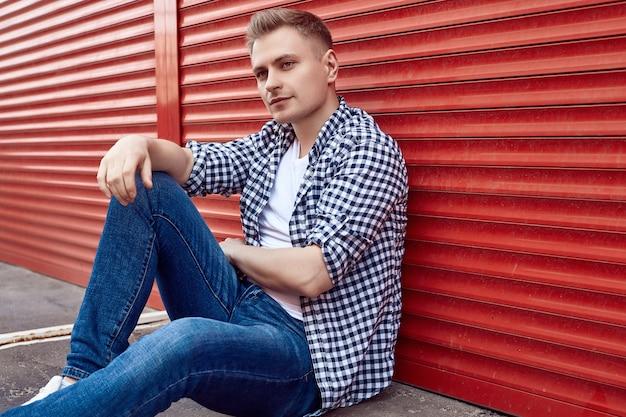Молодой красавец в рубашке и джинсах возле красных ворот Premium Фотографии