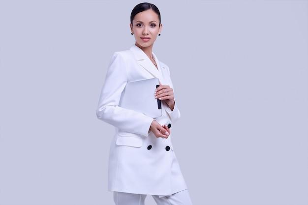 デジタルタブレットでファッションの白いスーツでゴージャスなラテン女性 Premium写真