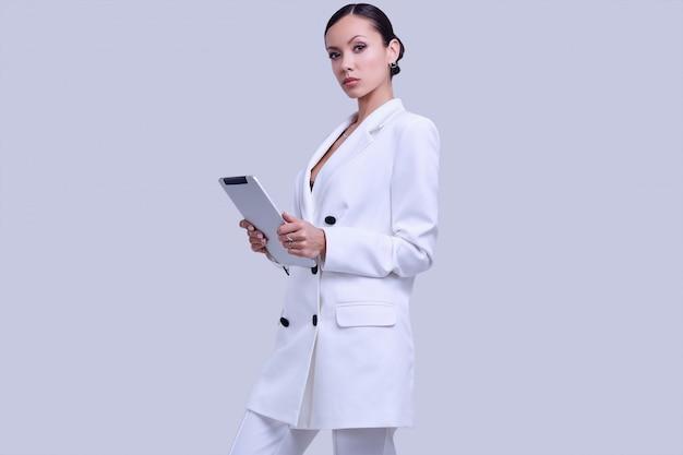 Великолепные латинские женщины в модном белом костюме с цифровым планшетом Premium Фотографии