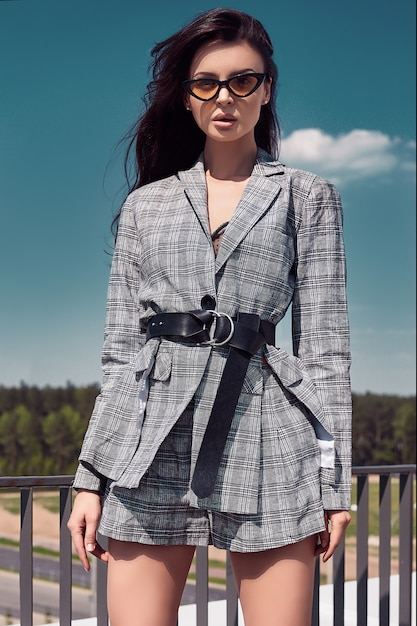 Очаровательная яркая брюнетка в шерстяном клетчатом деловом костюме Premium Фотографии