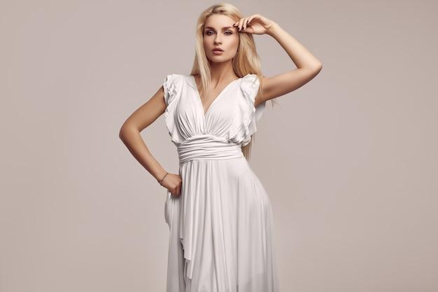 Великолепная чувственная блондинка в модном старинном белом платье Premium Фотографии
