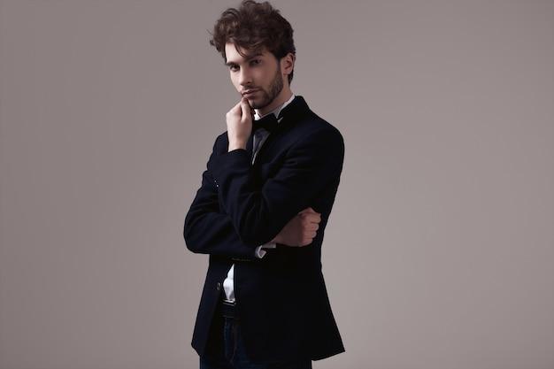 タキシードを着て巻き毛を持つハンサムなエレガントな男 Premium写真