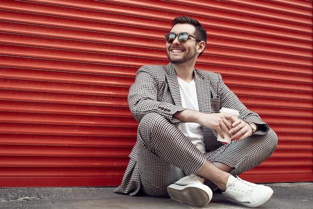 赤いゲートの近くのファッションスーツの若いハンサムな残忍な男 Premium写真