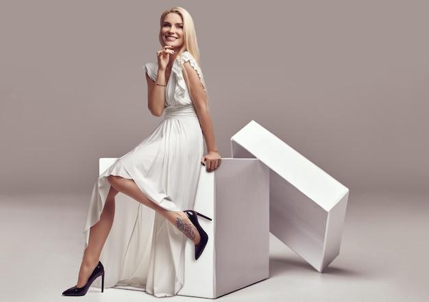 大きなショッピングボックスに白いドレスでゴージャスな官能的なブロンドの女性 Premium写真