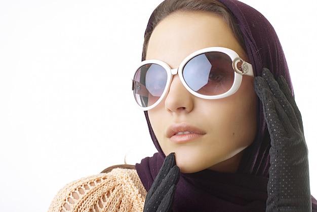 スタジオで眼鏡をかけたレトロなエレガントなファッショナブルな女性 Premium写真