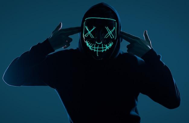 ネオンマスクの後ろに顔を隠して黒いパーカーの匿名男 Premium写真