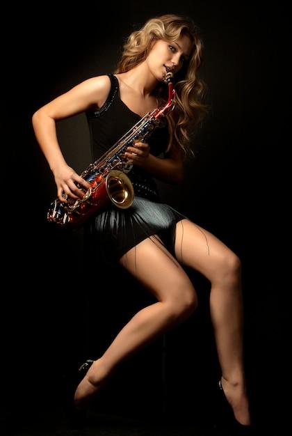 サックスとセクシーな魅力的な金髪の女性モデル Premium写真