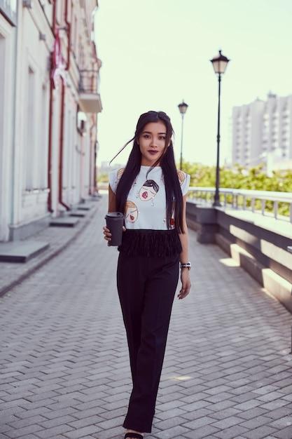 Шикарная азиатская женщина в платье моды гуляя вдоль яркой улицы Бесплатные Фотографии