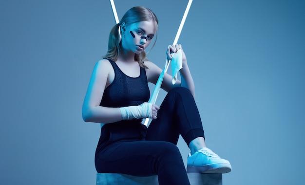Сильная красивая женщина со светлыми волосами, уверенным взглядом, кулаками в защитных боксерских повязках Premium Фотографии