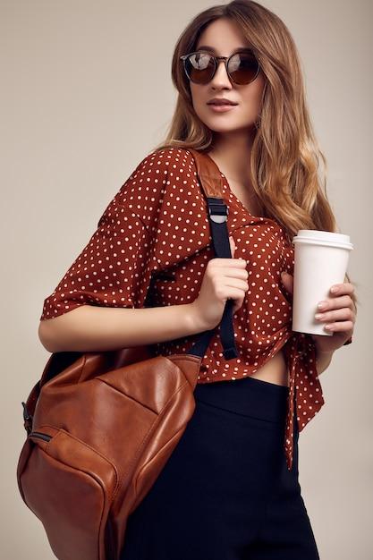 Улыбающаяся девушка студент битник с рюкзаком собирается в отпуск Premium Фотографии