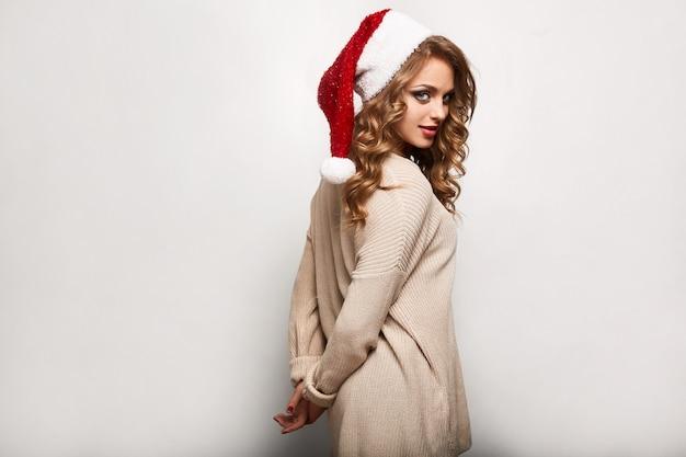 Красивая позитивная блондинка в свитере и праздничной кепке Premium Фотографии