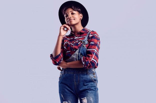 Элегантная черная хипстерская девушка с короткими волосами в клетчатой рубашке и джинсовом комбинезоне. Premium Фотографии