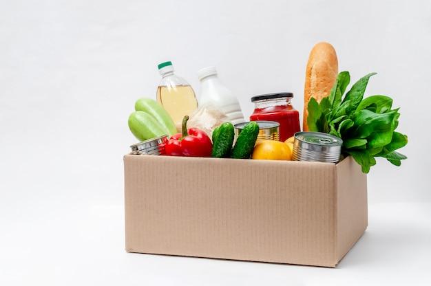 Коробка с продуктами питания. основные товары: масло, консервы, злаки, молоко, овощи, фрукты Premium Фотографии